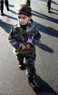 Très jeune enfant habillé en soldat, avec un bandeau extrémiste d'un groupe terroriste palestinien. L'éducation de la haine commence dès le plus jeune âge.